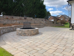 The construction of retaining walls on the slope allowed for a flat grade to install shrubs and ornamentals which provide a nice backdrop for this entertainment space.