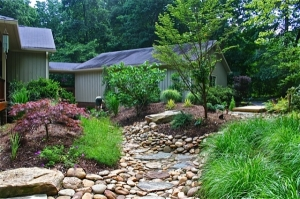Dry creek beds consisting of river rock and boulders are a great addition to woodland gardens.  Not only do they assist in achieving proper drainage in challenging areas, but they also add great natural aesthetics.