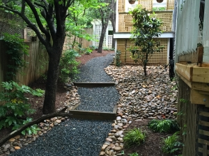 Areas on your property that don't get a lot of sunlight and are often damp are prime areas for stone and shade gardens.  The river rock and gravel walk serve two functions: 1. The remediation of moisture as a lack of sunlight.  2. A functional walking path.  The addition of Ferns, Hostas, Fatsia and other shade tolerant perennials make this a beautiful and inviting space as you enter in to this backyard.