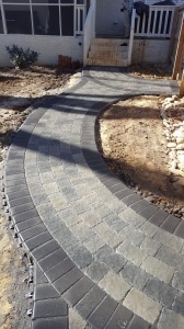 A simple paver leadwalk spanning from a detached garage offers functionality and beauty to this backyard renovation.