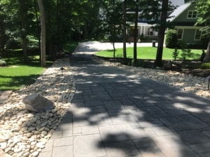 Concrete driveways and asphalt will eventually crack, leading to re-surfacing and patchwork.  Pavers will stand the test of time.  Adding a river rock boarder gives this driveway a more natural look.