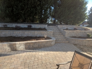 This paver patio backed up to a slope.  The construction of retaining walls on the slope allowed for a flat grade to install shrubs and ornamentals, providing a nice backdrop for this entertainment space.